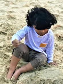 E loves playing in sand and I know she needs a haircut very badly